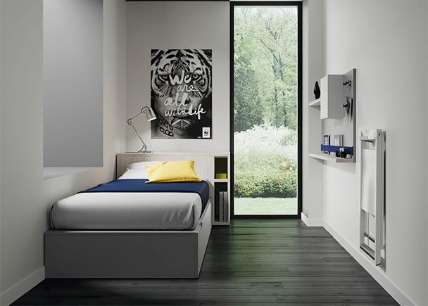 Dormitorio juvenil con cama nido y arcón con mesa extraible en el cabezal. El recto del ambietne se compone de unos modulos complementarios colgados en l