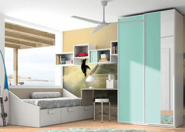 <p>Dormitorio infantil con armario de 122,1 de ancho y puertas correderas.</p> <p></p> <p>Junto al mismo se sitúa la mesa de estudio, formada por un sobre recto de 100 x 53 cm de fondo, que encuentra su apoyo gracias a la escuadra de unión que la sujeta al armario, y a un costado especial que la sujeta a la cama compacta.<br />Esta cama es el modelo divano para somier de 90 x 190, que incorpora 3 cajones en su base..<br />Sobre la pared hemos realizado una composición mural, jugando con estantes diáfanos de línea cúbica.</p>