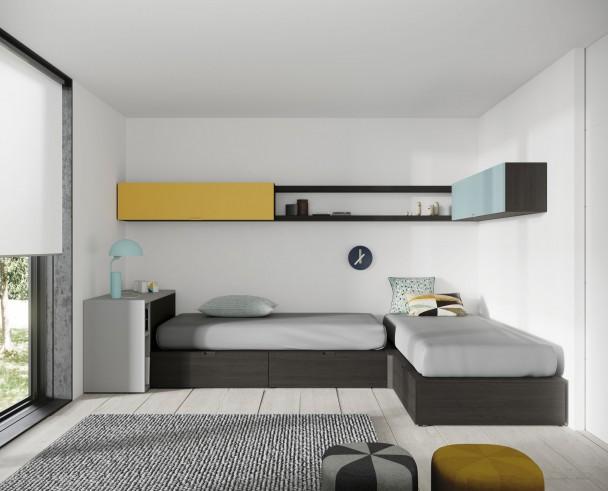 <p>Dormitorio juvenil con dos camas tipo cubo dispuestas en &aacute;ngulo, con m&oacute;dulo rinc&oacute;n de enlace. En la cabecera de una de las camas, se ha colocado un m&oacute;dulo que contiene una mesa extraible. El ambiente se completa con unos colgantes horizontales y unos estantes de pared..</p>