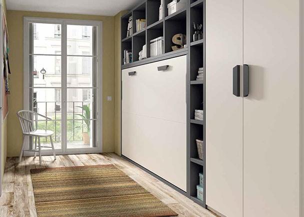 <p>Estudio con cama abatible horizontal de 135 x 190 con librería superior y lateral a base de celdas simétricas realizadas en tono contrastado. El ambiente se completa con un armario recto de dos puertas.</p>