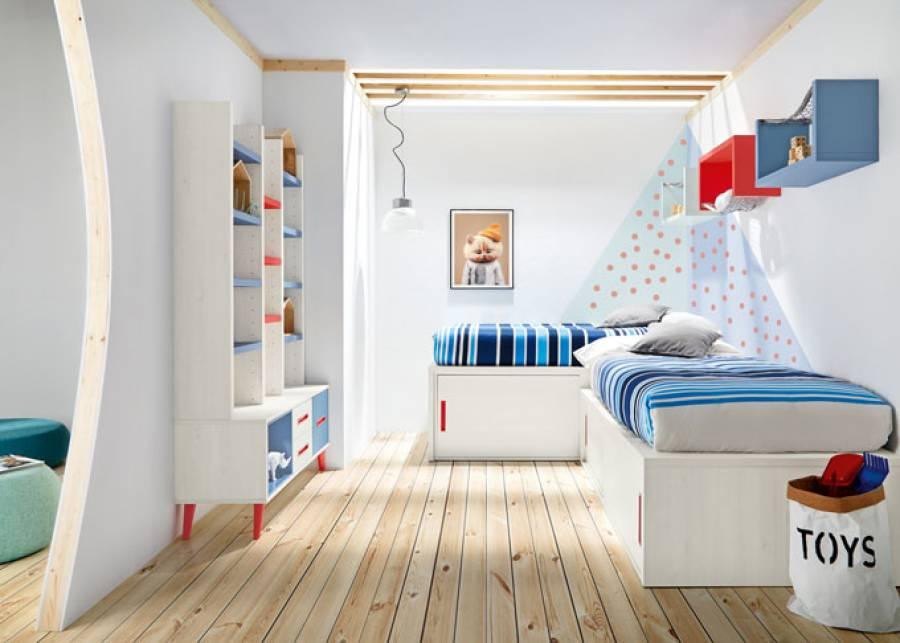 """<p>Habitaci&oacute;n infantil compartida, equipada con dos camas dispuestas en """"L"""" con base de puertas correderas. En la pared frontal se ha colocado un mueble librer&iacute;a con base de cajones sobre pata n&oacute;rdica.&nbsp;</p>"""