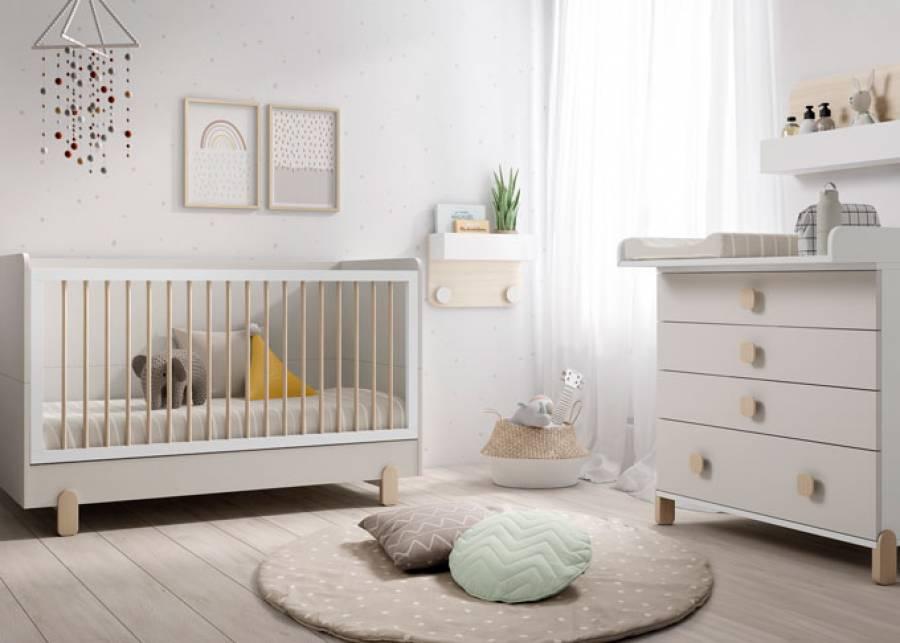 Cuna infantil para medida de colchón de 140x70, con patas de haya y barandillas de barrotes. Una barandilla es fija y la otra es móvil. El somier