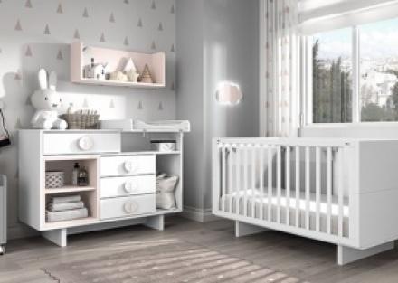 Dormitorio para bebés con una cuna con ruedas de barandilla deslizante y cajón inferior